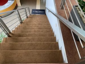 Pokládáme i běhoun na schody. V tomto případě byla pokládka doplněna i o rohožku s vlastním potiskem s logem firmy.