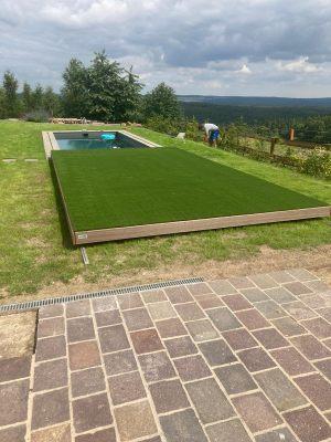 Tráva Rosemary na pojízdné terase. Pojízdná terasa pokrývá bazén a pojízdnou terasu pokrývá umělá tráva, která je velice hustá a příjemná na omak.